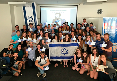 Large group of students are shown holding an Israeli flag during their training to help censor the internet by using their social media tool, ACT.IL.