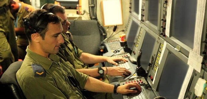 Men in uniforms sit in front of a command center, the elite spy arm is known as Unit 8200.