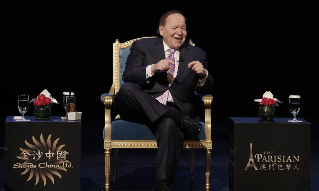 Sheldon Adelson sits on a stage. He is a campaign contributor to Trump, and donors like him contribute to the pressure for major support of Israel such as the $38 billion minimum requirement.