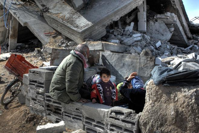 A family sits in the ruins of their home, 2009