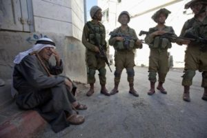 Tired Palestinian old man surrounded by Israeli soldiers. Candidates ignore Israeli constant encroachment on Palestinian lives