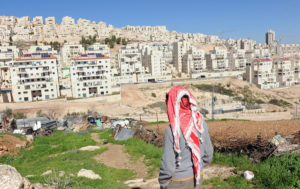 Palestinian looks at an Israeli settlement on stolen Palestinian land. Candidates will not acknowledge the settlements' illegality.