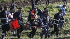 Palestinian paramedics carry wounded protester