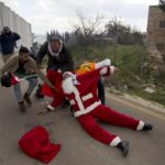 A Palestinian protester wearing a Santa Claus costume is carried by medics after inhaling tear gas fired by Israeli troops during clashes at Bethlehem checkpoint in the West Bank city of Bethlehem, Tuesday, Dec. 23, 2014.