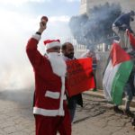 A Palestinian protester dressed in a Santa Claus costume rings a bell in front of tear gas fired by Israeli troops during a demonstration against the settlements and demanding for free movement for the Palestinians during Christmas near a checkpoint in the West Bank city of Bethlehem December 23, 2014.