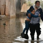 Gaza humanitarian crisis: A Palestinian man and boy navigate the streets of Gaza City, which are flooded with sewage.