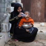 A Palestinian woman gives water to her son in Khan Younis in the southern Gaza Strip December 19, 2018.