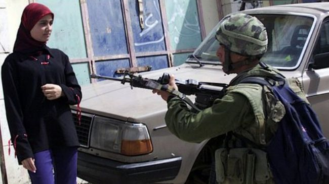 Israeli soldier holds Palestinian woman at gunpoint