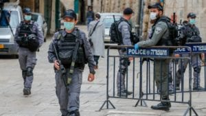 Israeli security forces, wearing protective masks as a precaution during the Covid-19 coronavirus pandemic, stand on guard in the old city of Jerusalem on the Orthodox Christian holiday of Holy Friday on April 17, 2020.