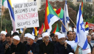 "Members of the Israeli Druze community and their supporters protest against the new nation-state law in Tel Aviv, with a sign that says ""when injustice becomes law, resistance becomes duty"""