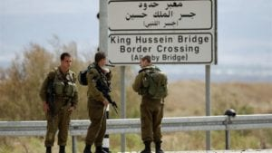 allenby bridge crossing sign with armed Israeli security personnel