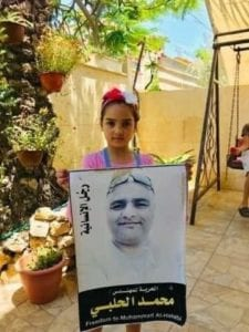 mohammad halabi's daughter holds a poster of her father