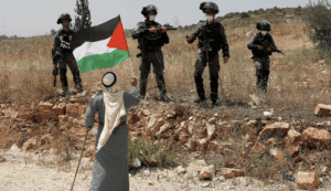 palestinian man with flag faces israeli soldiers