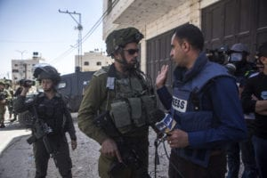 An Israeli soldier harasses a Palestinian journalist during a demonstration in solidarity with the Great March of Return in the West Bank city of Hebron in April 2018.