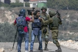 An Israeli soldier escorts a Palestinian journalist during a weekly demonstration, May 11, 2018