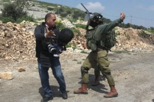 An Israeli soldier attacks AFP'S photo journalist Jafer Eshtayah during a protest, March 22, 2019