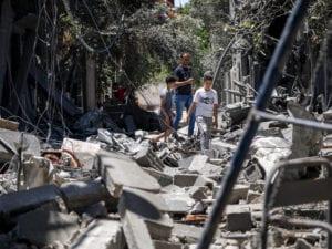 gazan children view a destroyed neighborhood