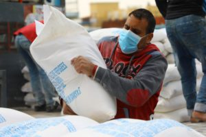 palestinian man carrying a bag of flour from UNRWA