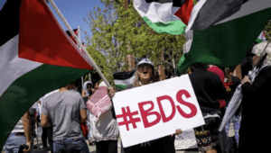 """A woman yells while holding a sign """"#BDS,"""" referring to """"Boycott, Divestment, Sanctions,"""" in front of the Israeli Consulate in Los Angeles on May 14, 2018"""